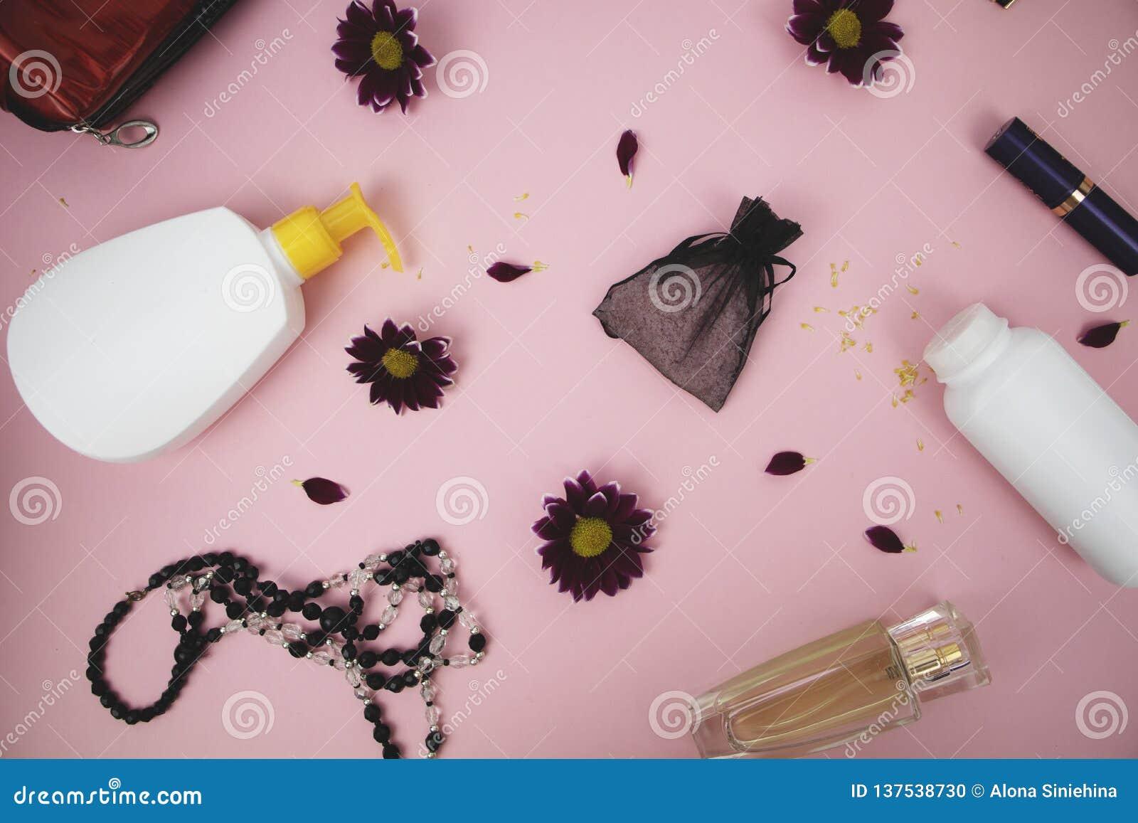 在桌上的化妆用品在妇女 化妆袋子、化妆用品和卫生学方面的产品 文本的桃红色背景