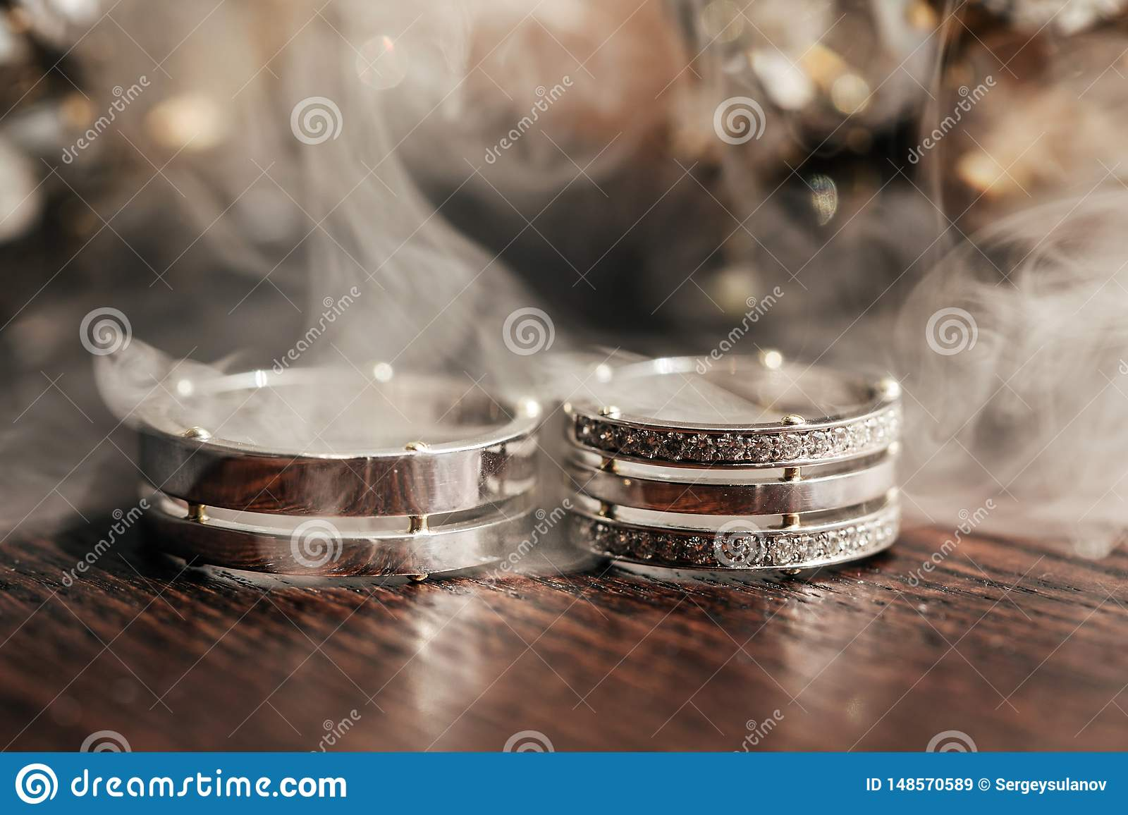在桌上的婚姻的白色圆环与烟