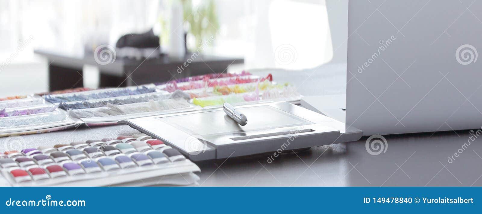 ?? 在桌上的笔、笔记本和织品样品在名牌服装