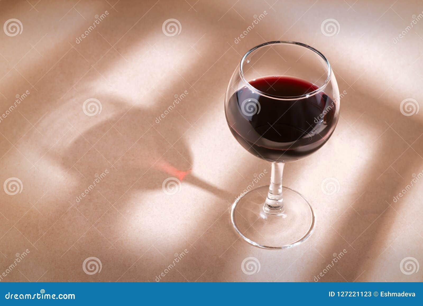 在桌上的红葡萄酒玻璃与窗口阴影