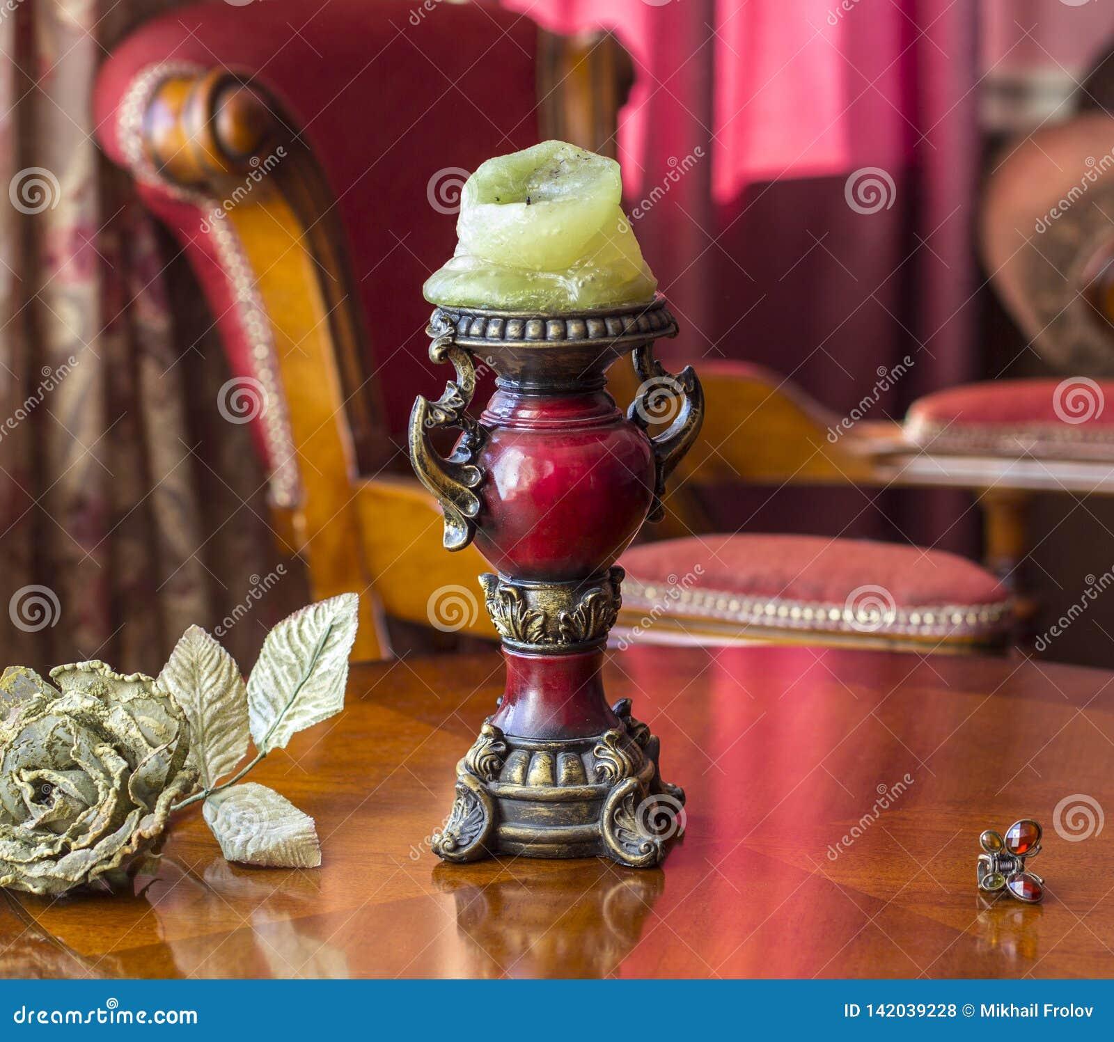 在桌上的葡萄酒烛台在一朵人为玫瑰和一把簪子旁边在蝴蝶的想法 古典内部