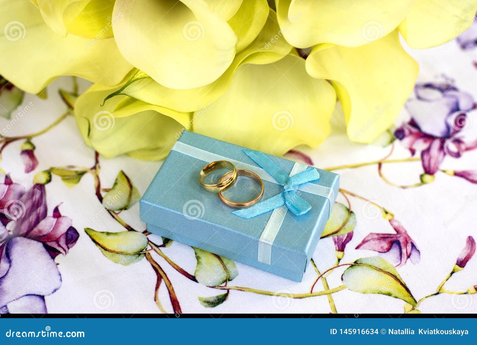 在桌和花束上的结婚戒指