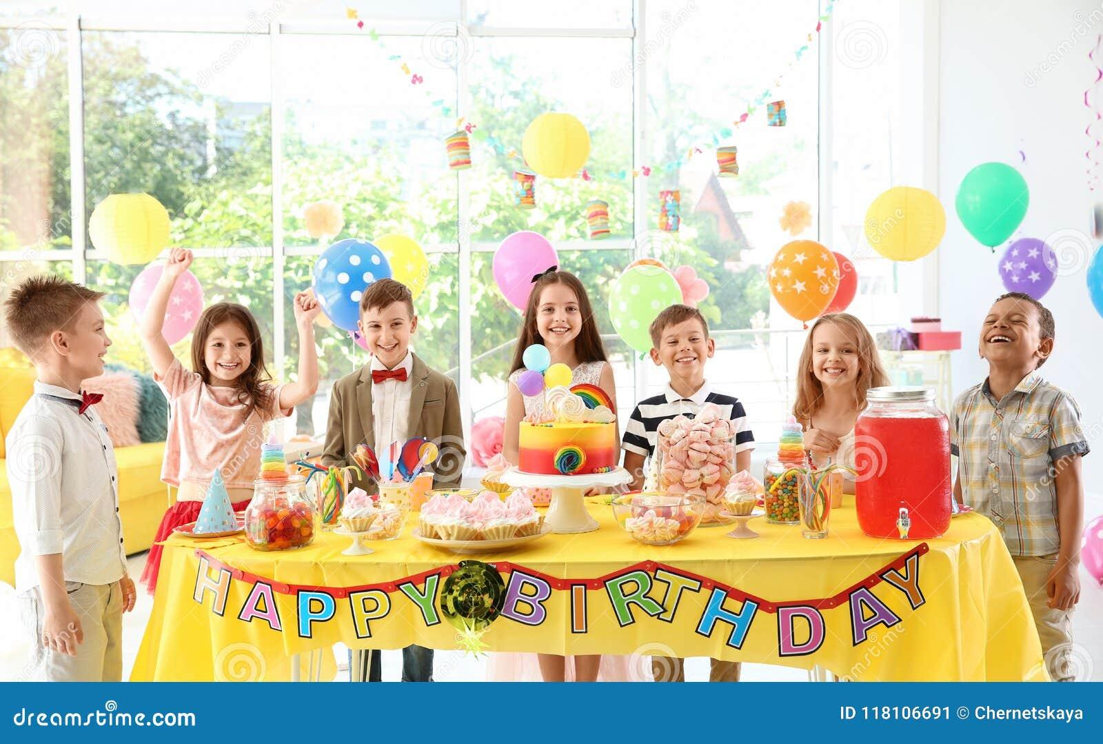 在桌附近的逗人喜爱的孩子与在户内生日聚会的款待