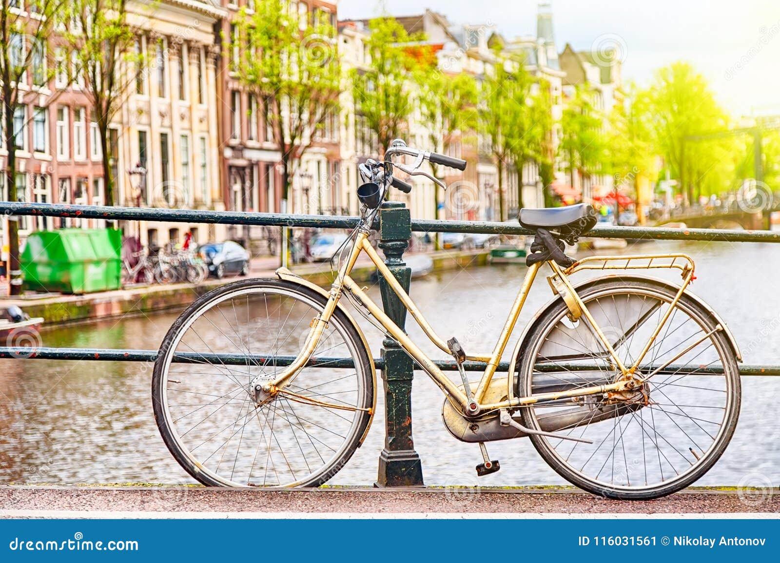 在桥梁的减速火箭的bycicle在阿姆斯特丹,反对运河的荷兰 阿姆斯特丹明信片 蓝色汽车城市概念都伯林映射小的旅游业