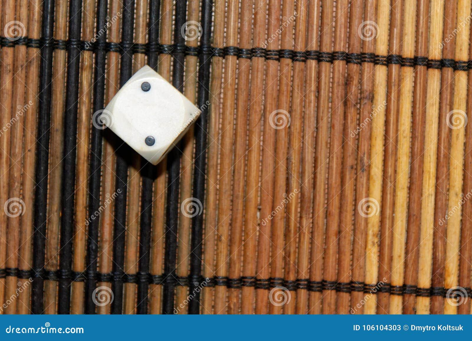 在棕色木板背景的一个白色塑料模子 与黑小点的六个边立方体 第2