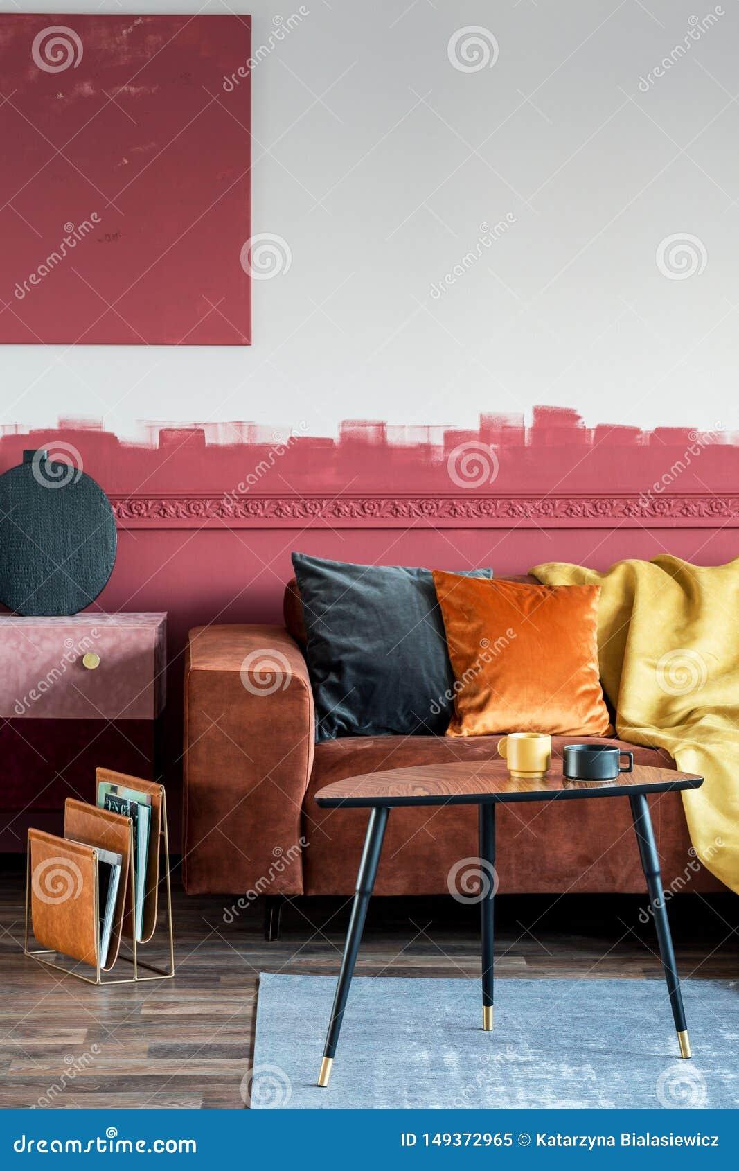 在棕色沙发的橙色枕头在与绒面革洗脸台和木咖啡桌的时兴的客厅内部