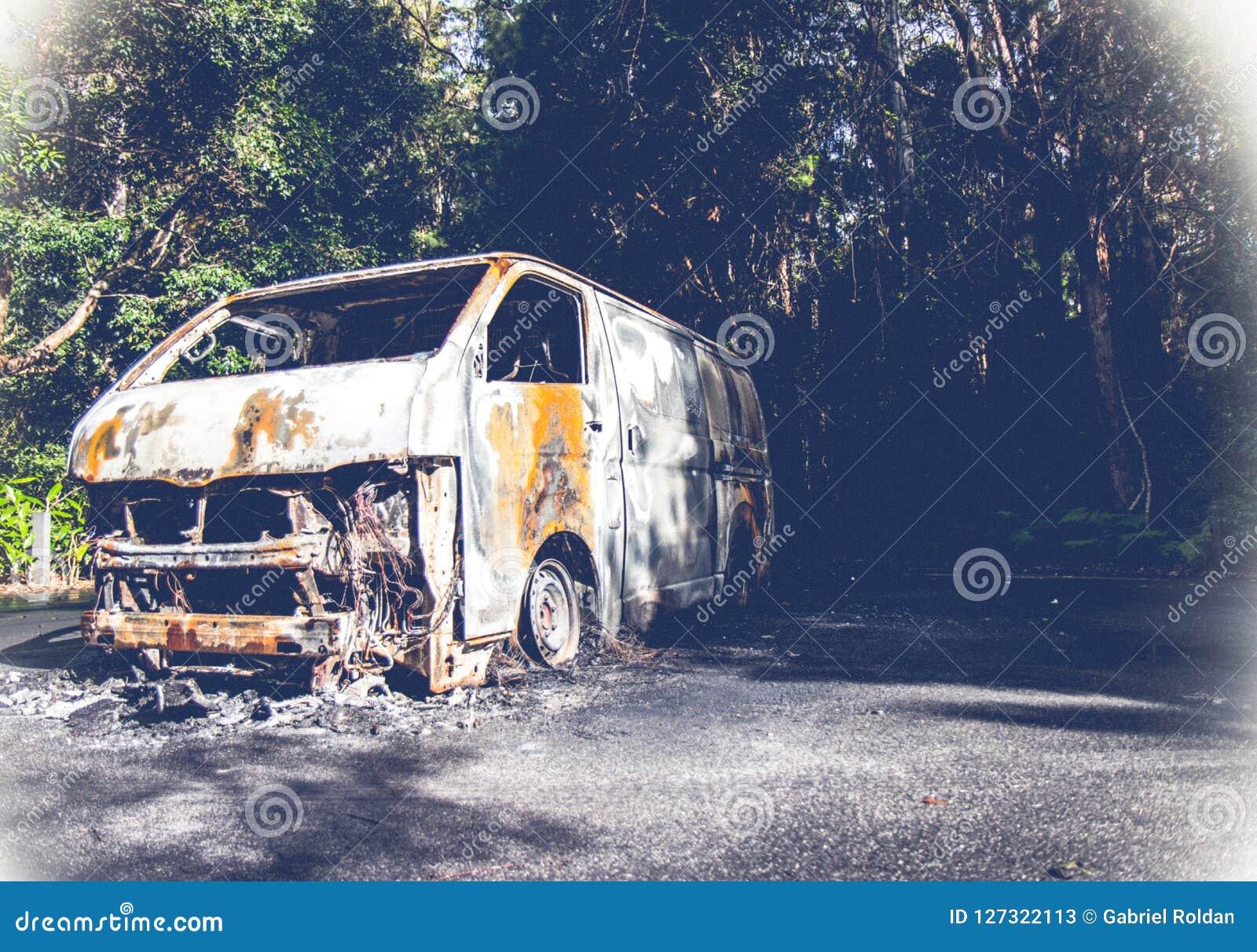 在森林公路的被击毁的老车