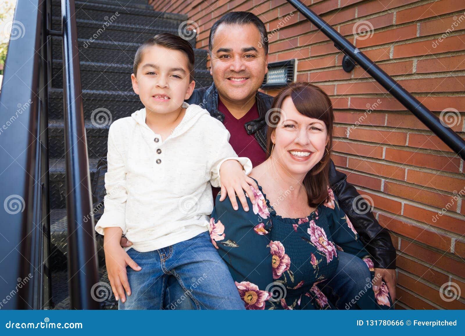 在楼梯的混合的族种年轻家庭画象