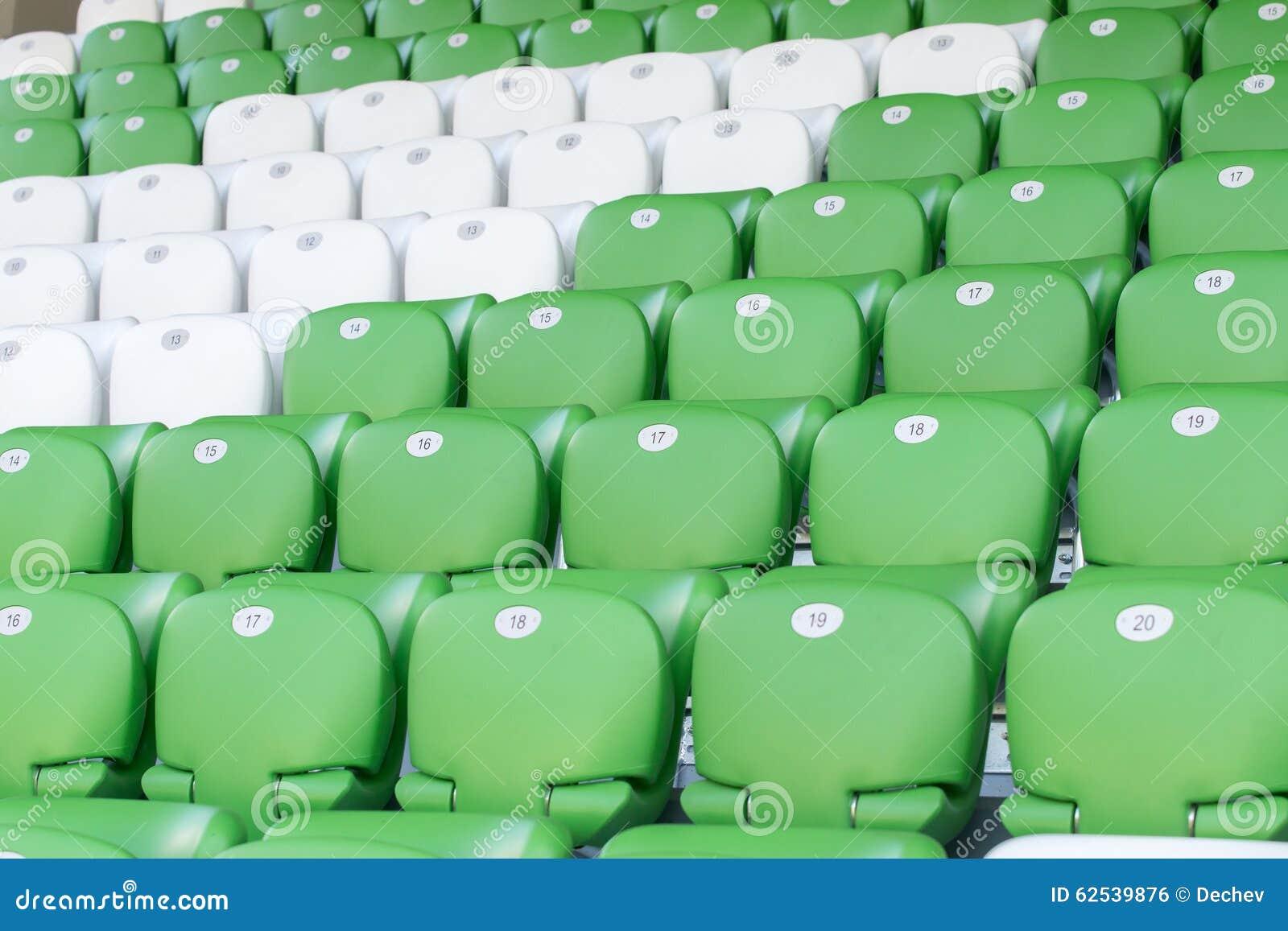 在橄榄球场的塑料绿色和白色位子