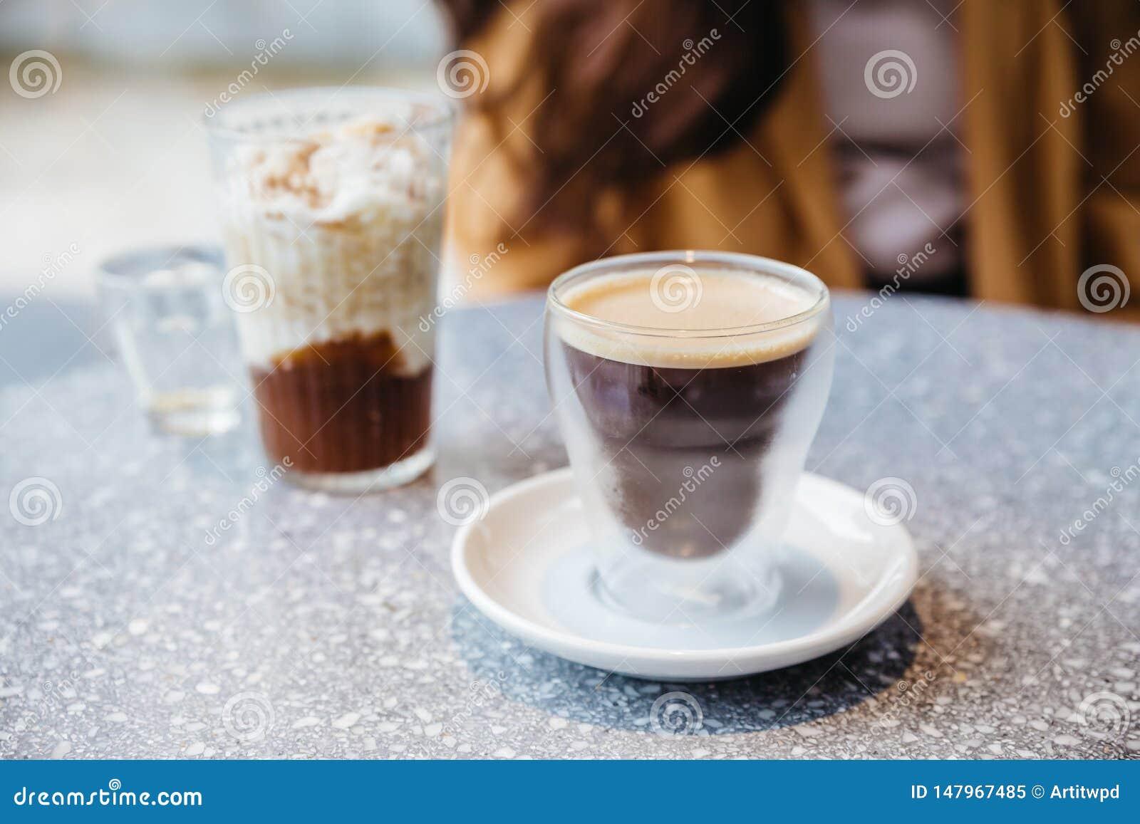 在水杯的泡沫的硝基冷的酿造咖啡在花岗岩上面桌上有迷离背景