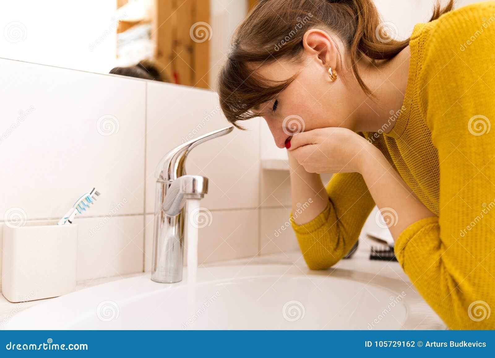 在水槽附近的年轻呕吐的妇女在卫生间里