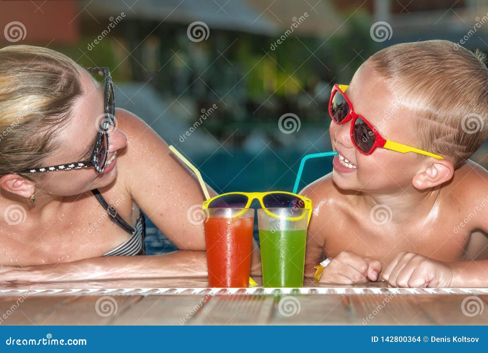 在水池的母亲和儿子饮用的鸡尾酒 热的暑假