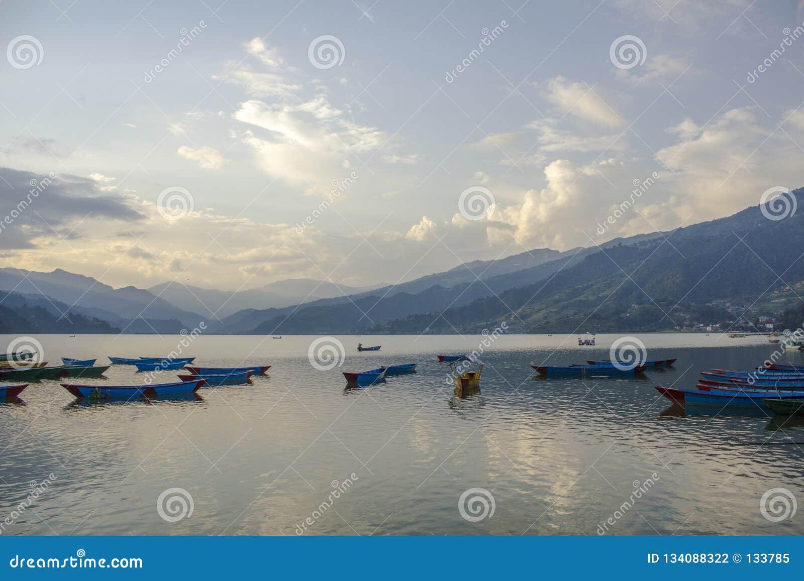 在水的蓝色红色黄绿色老木小船 在湖的划艇反对绿色山背景在的