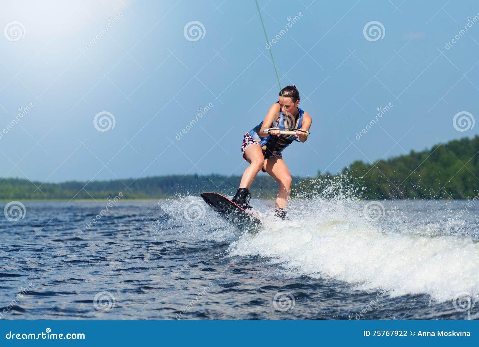 在汽艇波浪的亭亭玉立的深色的妇女骑马wakeboard在湖