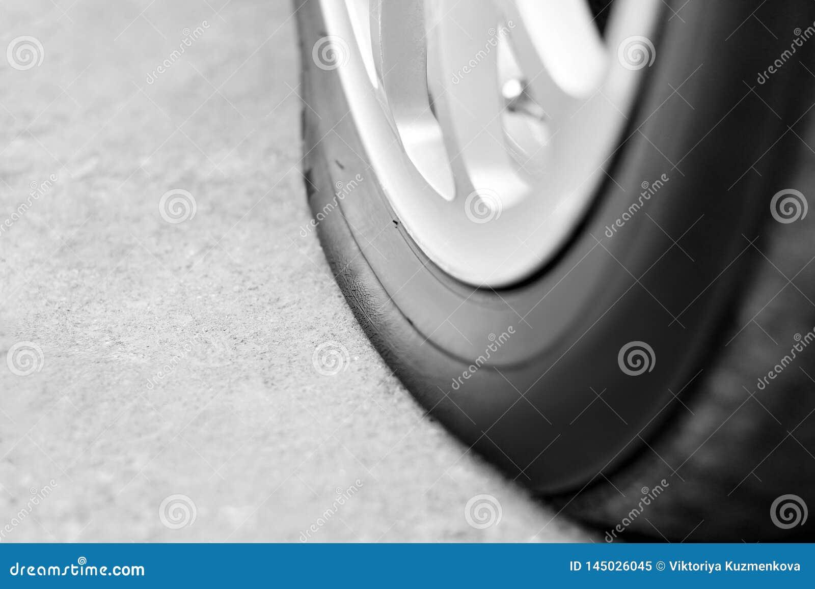 在汽车的泄了气的轮胎 银色伪造的轮子 ??