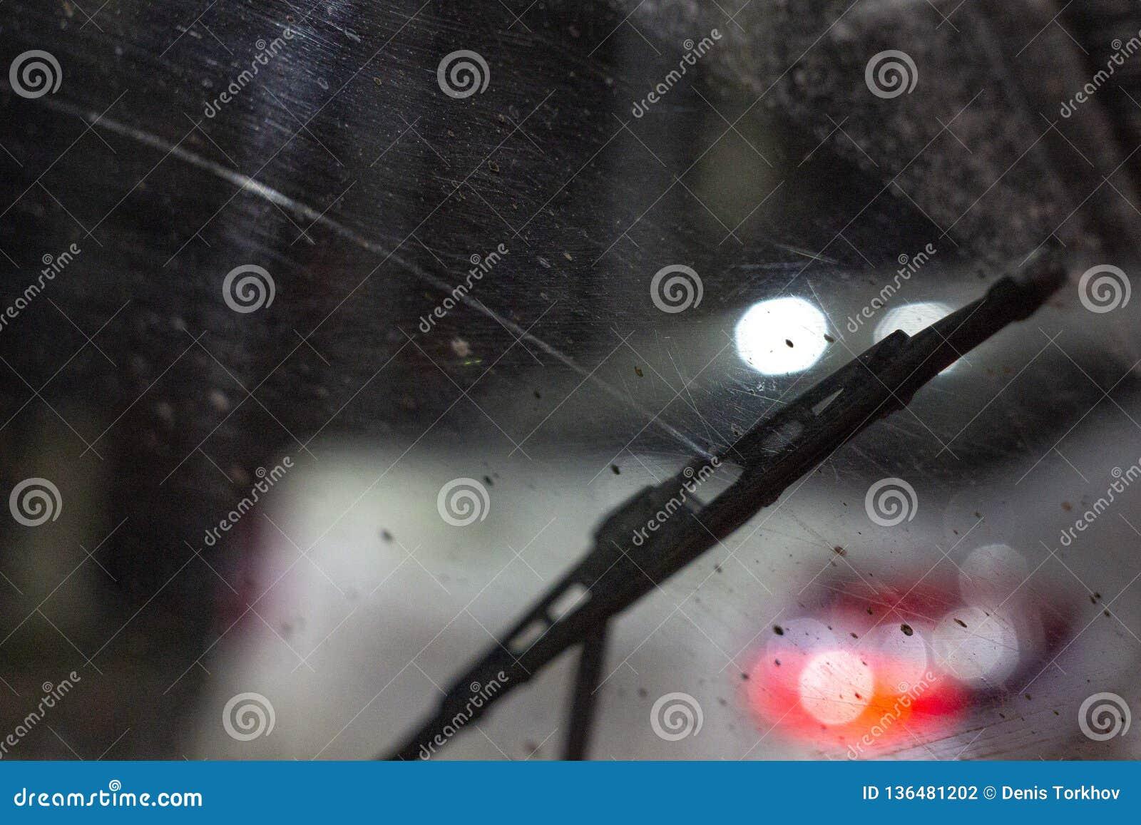 在汽车里面的刮水器在一块肮脏的被抓的挡风玻璃,雨季节,在晚上 前面和后面背景弄脏与