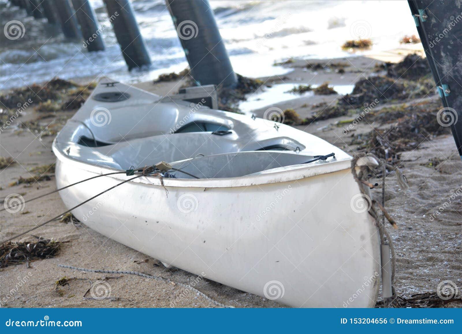 在沙子的一条美丽的白色小船在跳船下