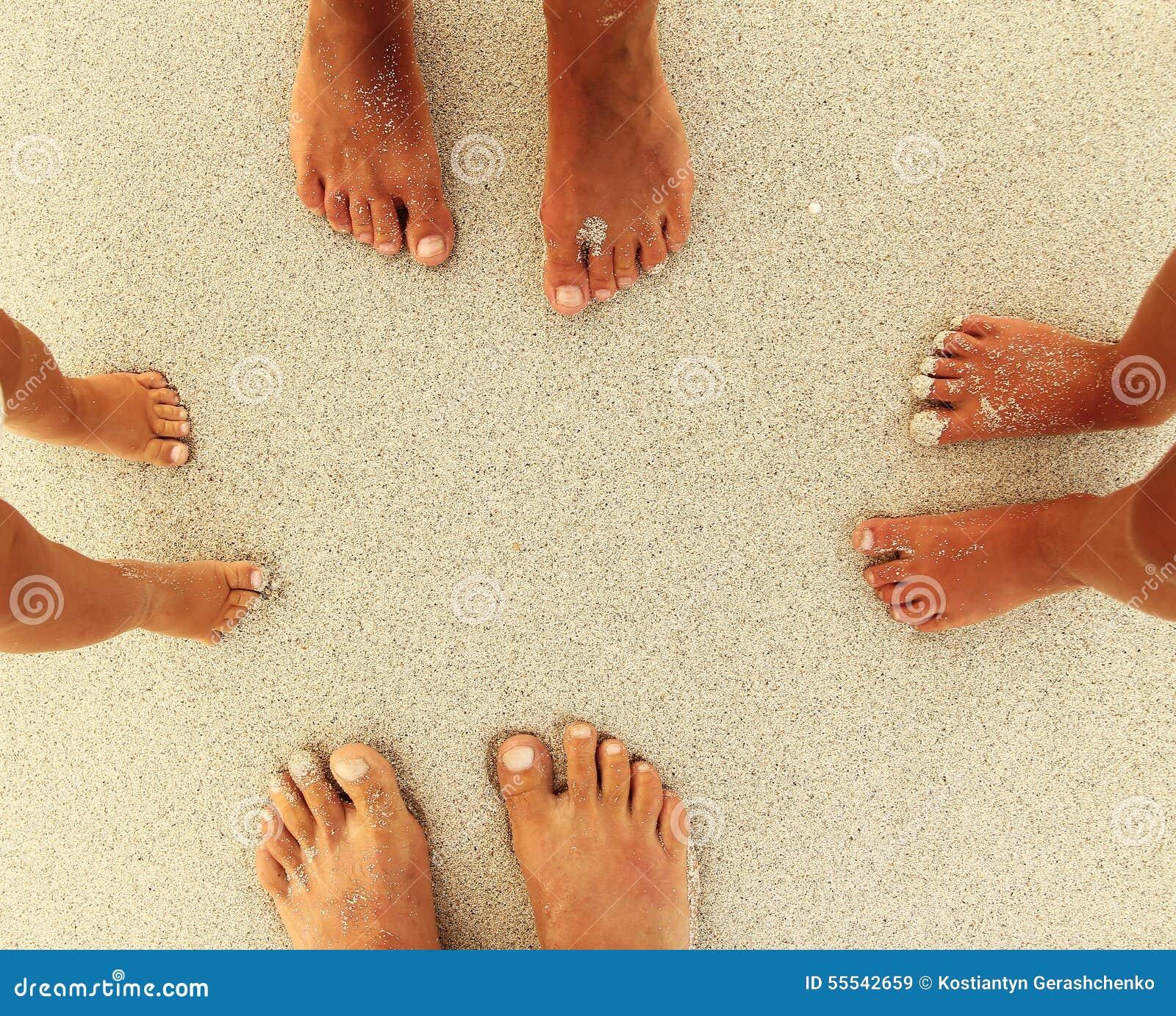 在沙子的家庭脚在海滩
