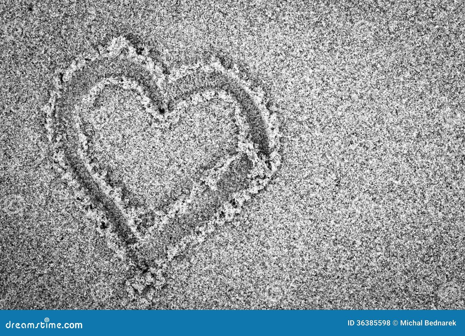在沙子的心脏形状。浪漫,黑白