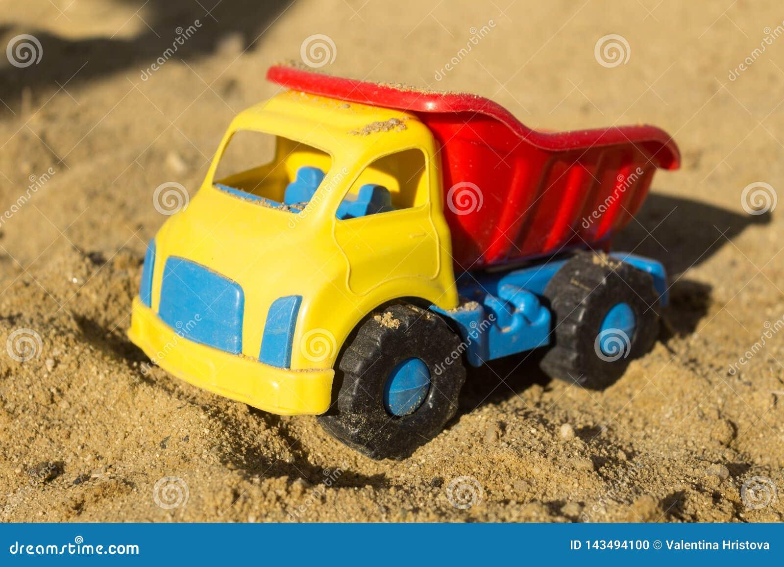 在沙子的黄色红色和蓝色卡车玩具,在海滩
