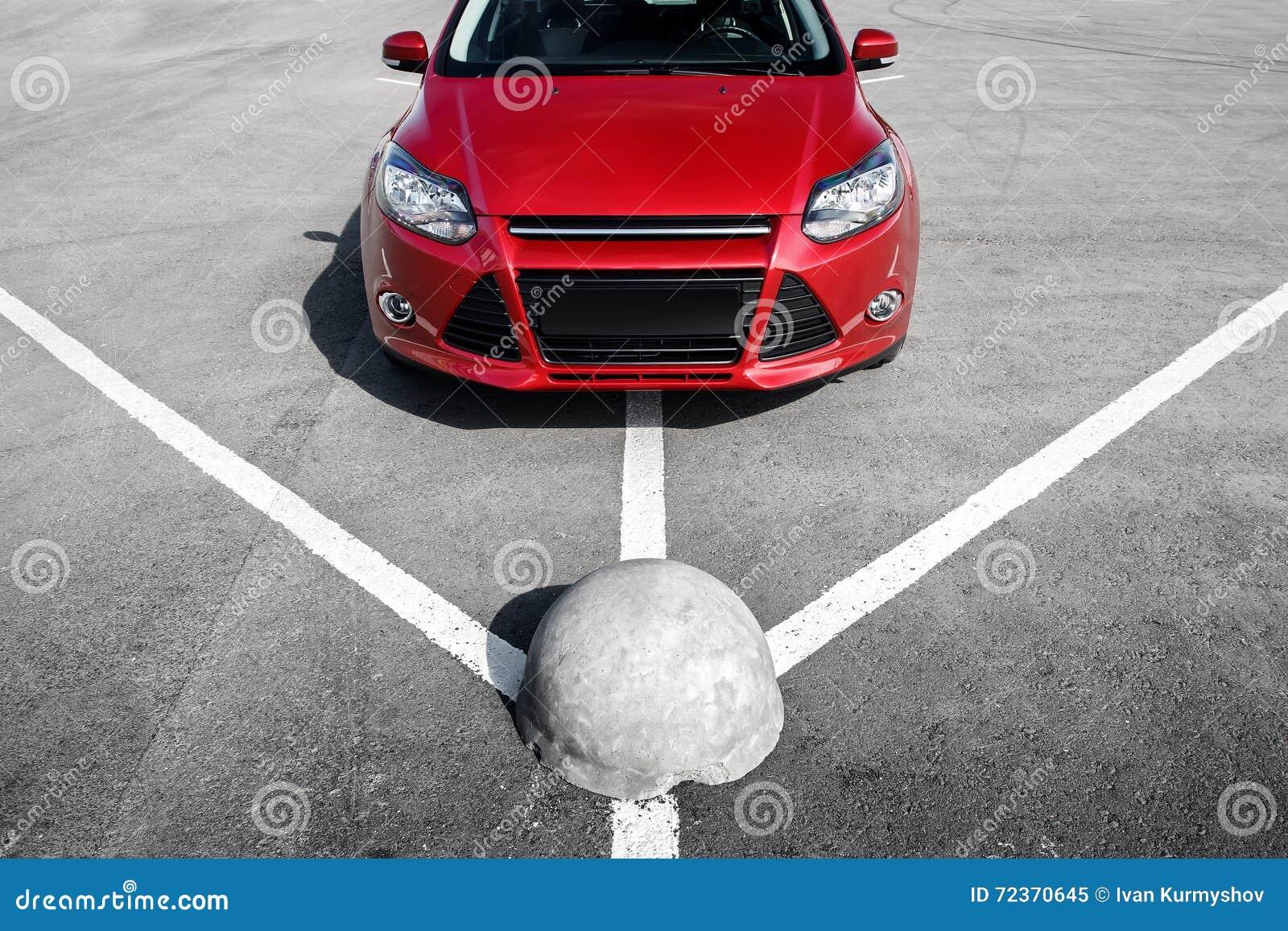 在沥青停车处的红色汽车在白天