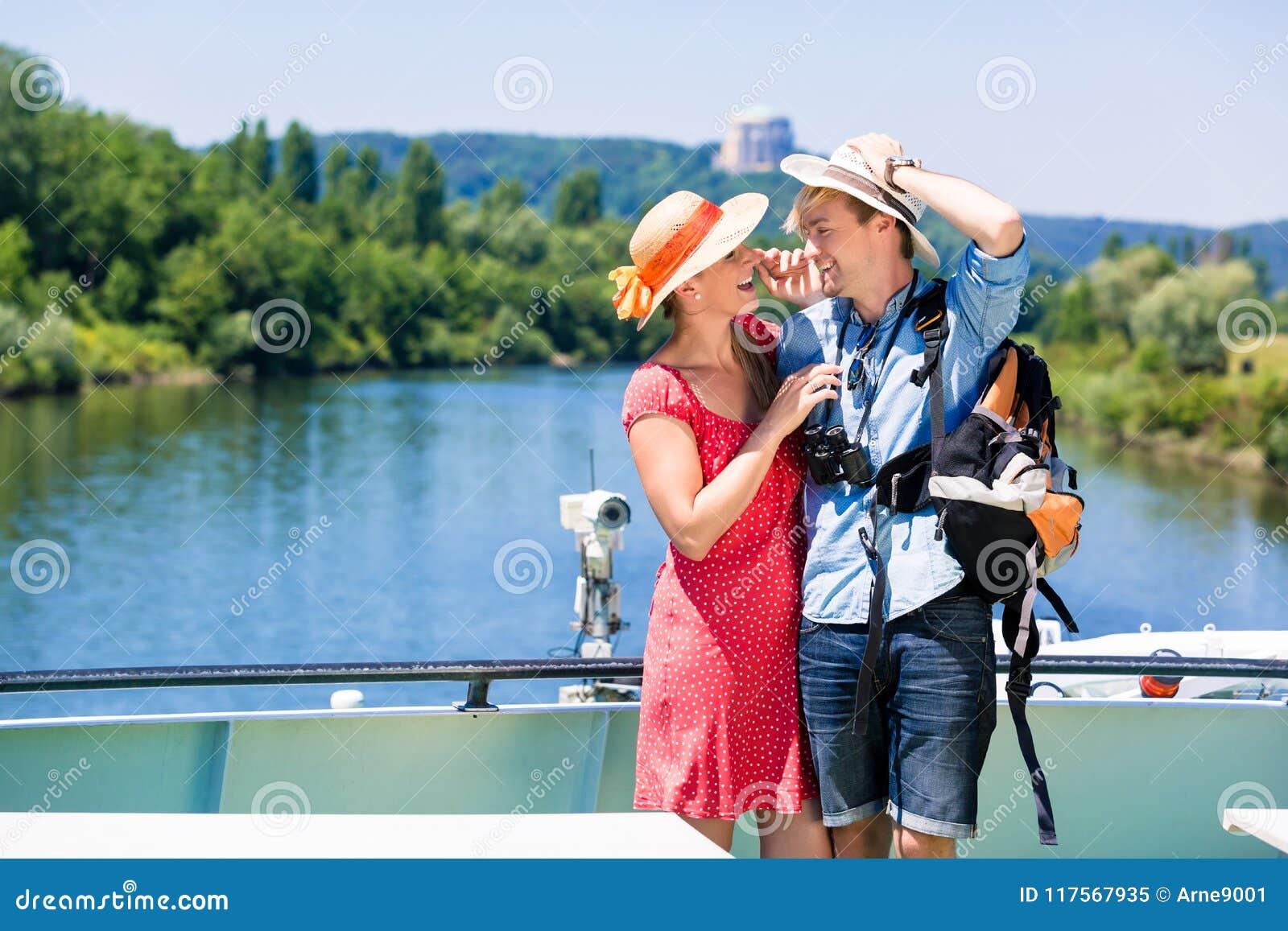 在河巡航佩带的太阳帽子的夫妇在夏天