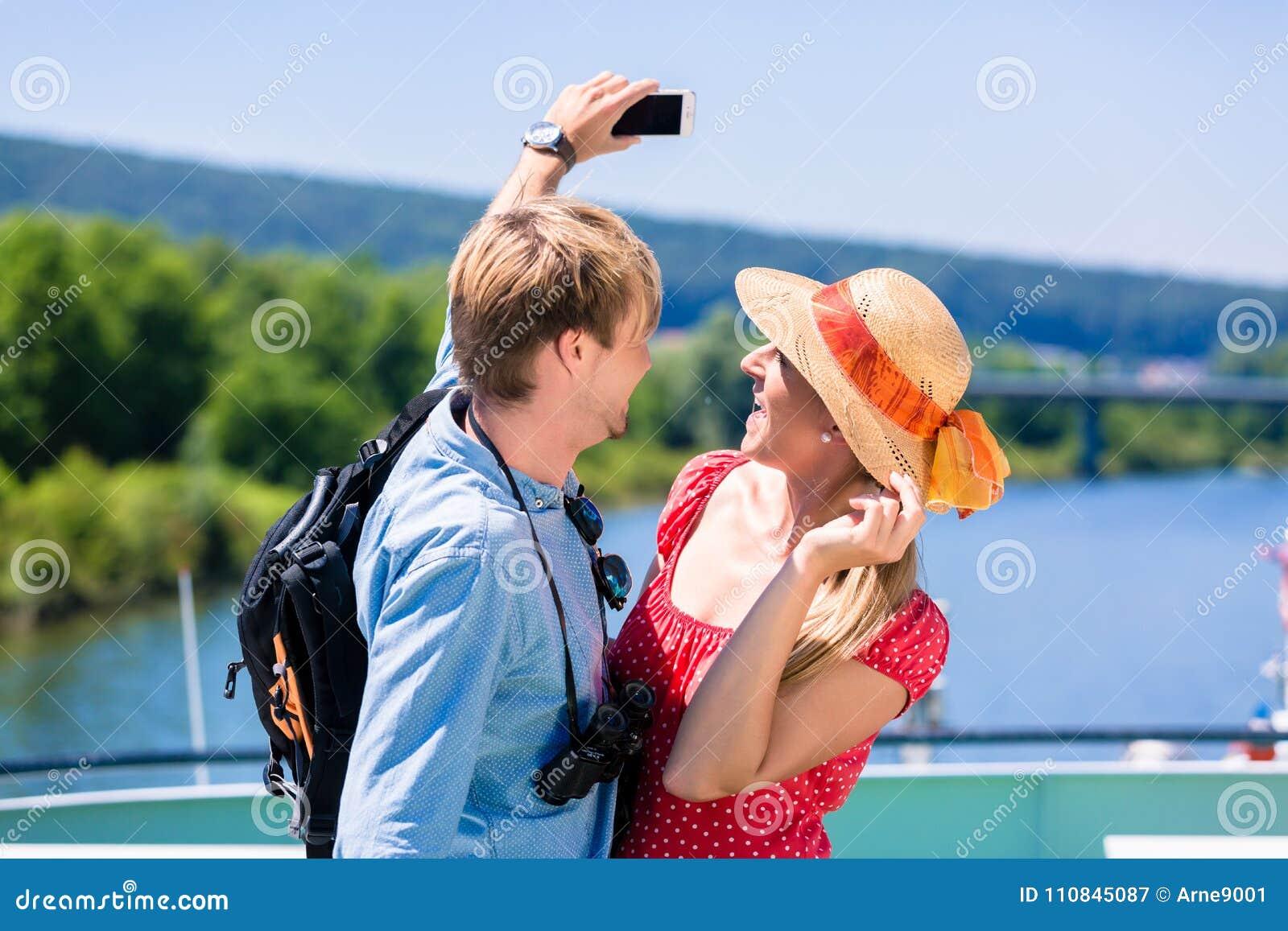 在河的年轻夫妇在采取selfie的夏天巡航