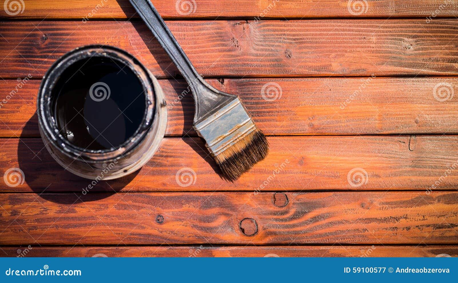 在油漆罐头旁边的老使用的画笔