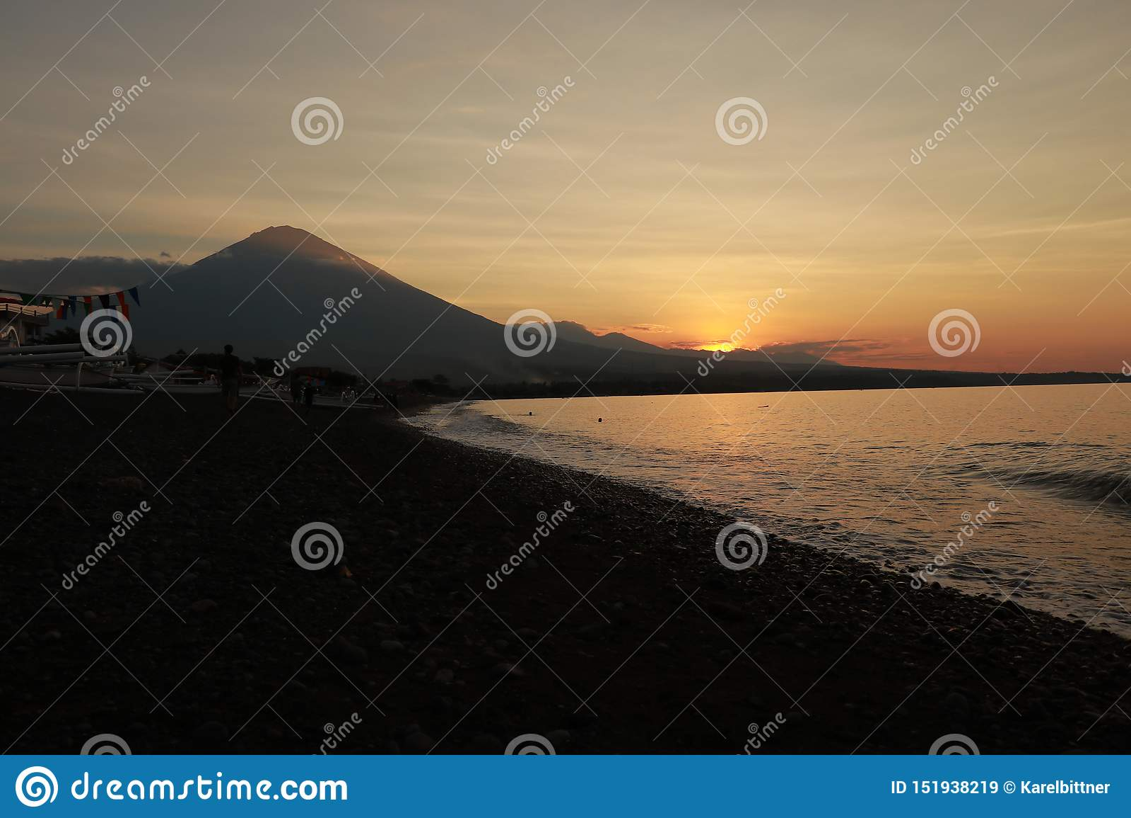 在沿海的浪漫日落在印度尼西亚 冲浪者去享用paddleboard在日落 有庄严火山的海岸线全景