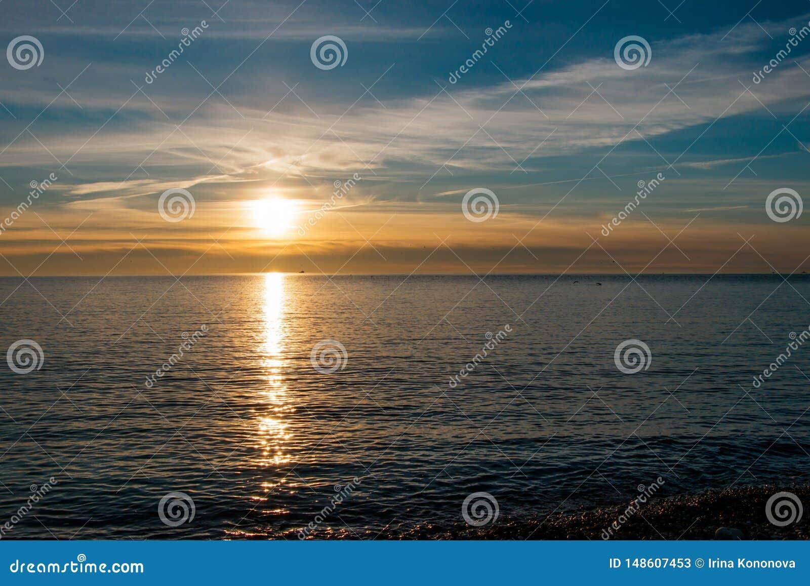 在沿海的美好和明亮的日落在蓝色和黄色口气