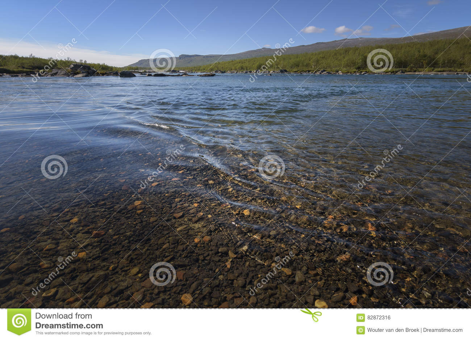 在流动的水的美好的镇静波纹与惊人的着色河底石头