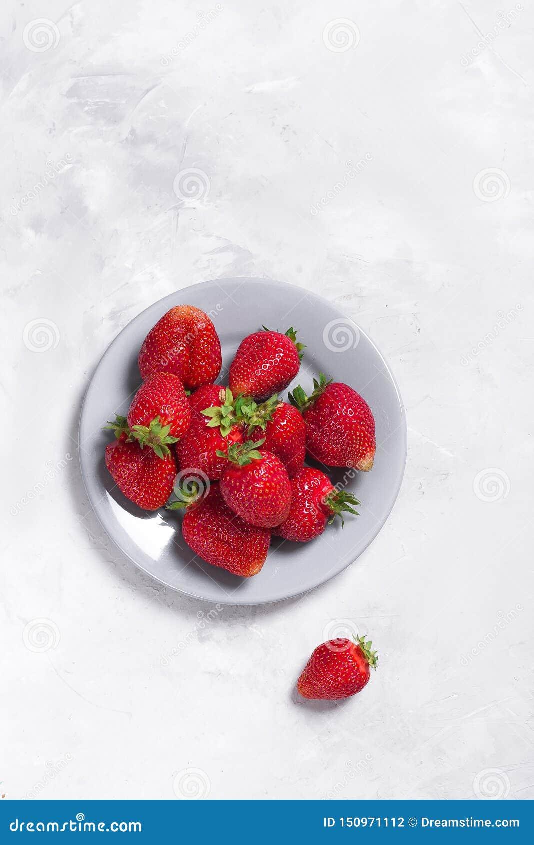 在浅灰色的背景的大新鲜的草莓