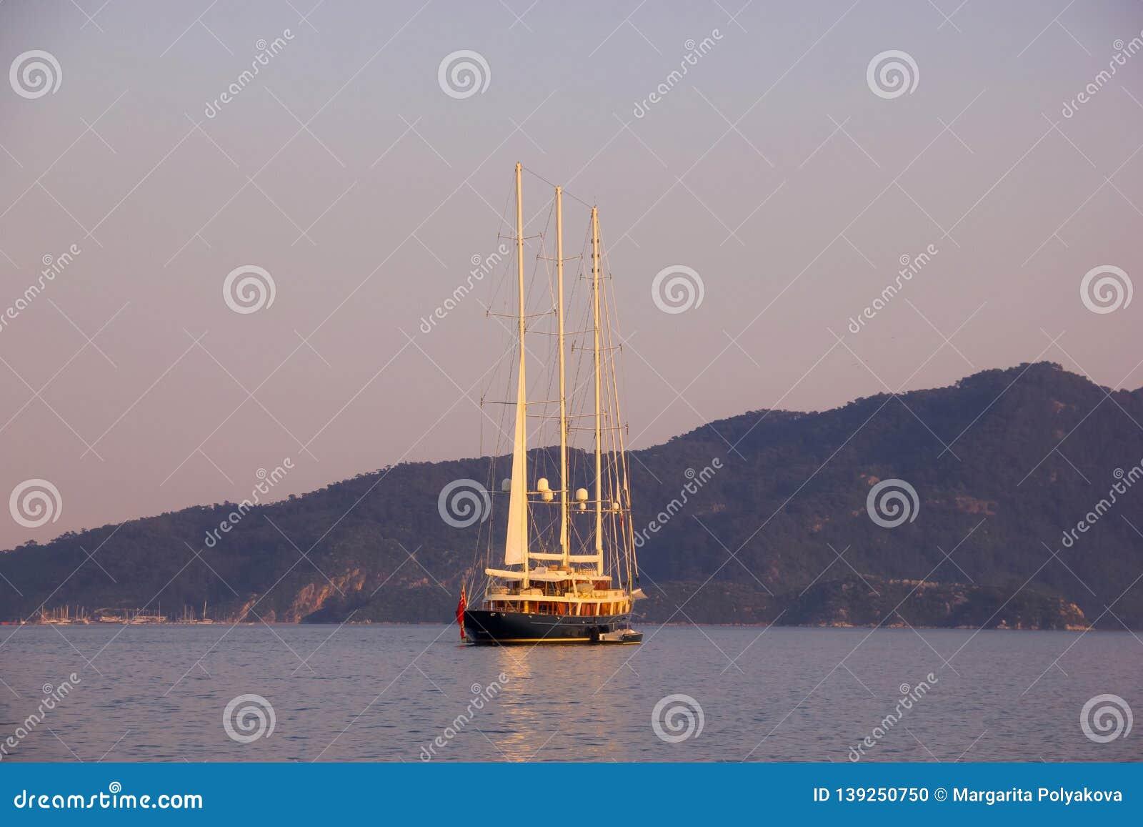 在海、日落和山的美丽的风船在背景中
