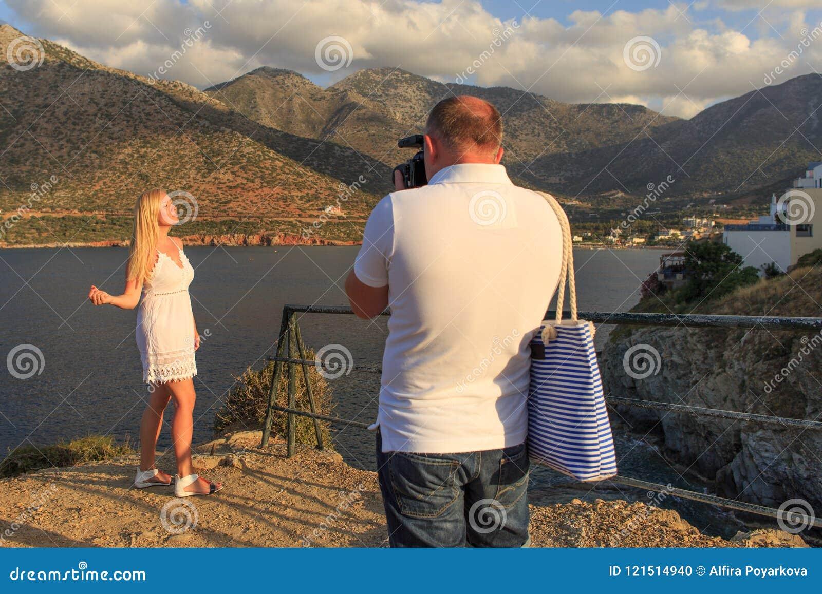 在海和山附近供以人员为他的女朋友照相