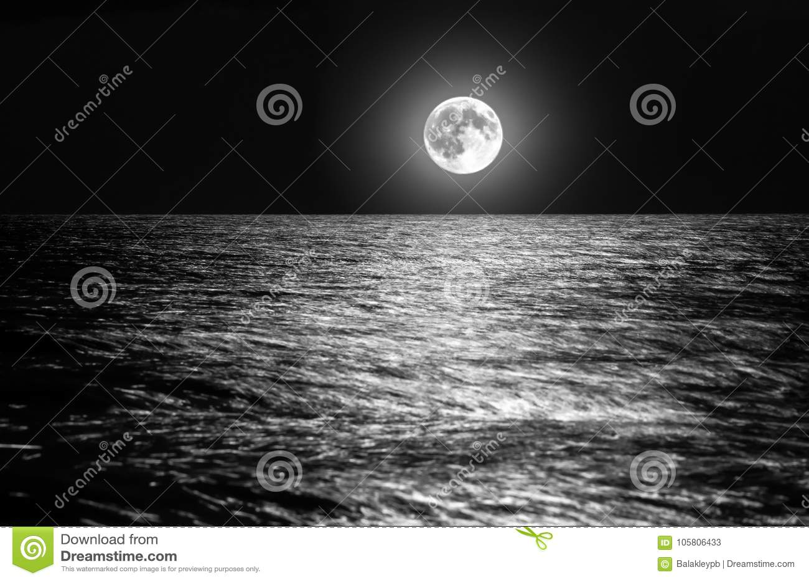 在海天线的月亮在晚上 在波浪的月光
