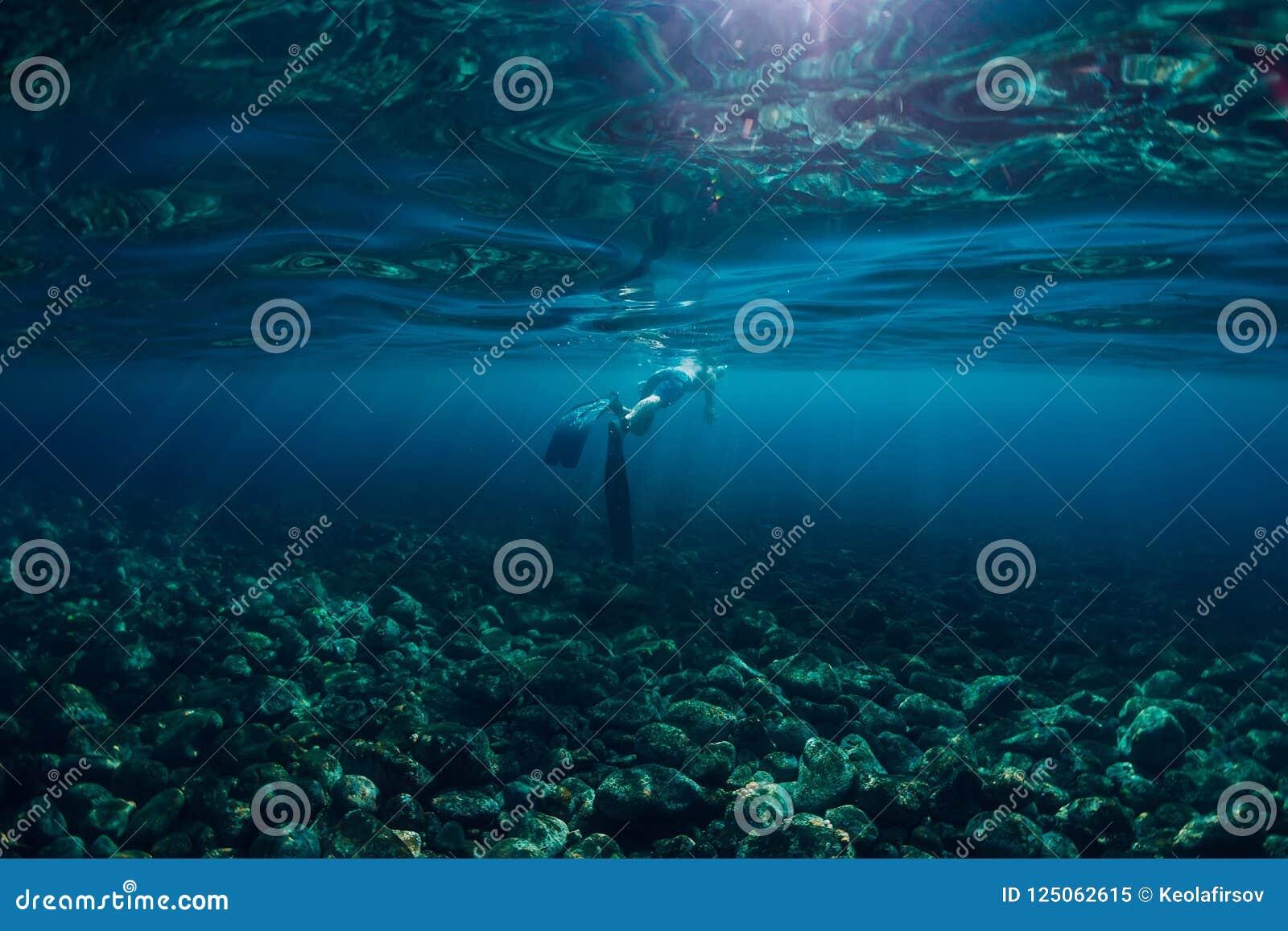 在海洋、水下的照片与阳光和深度的Freediver游泳