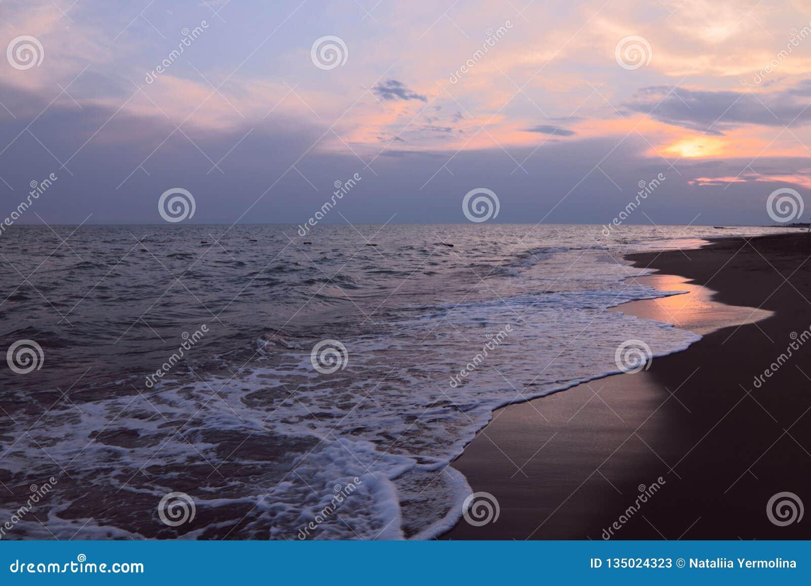 在海洋的多云日落天空 在日落的迷人的天际线