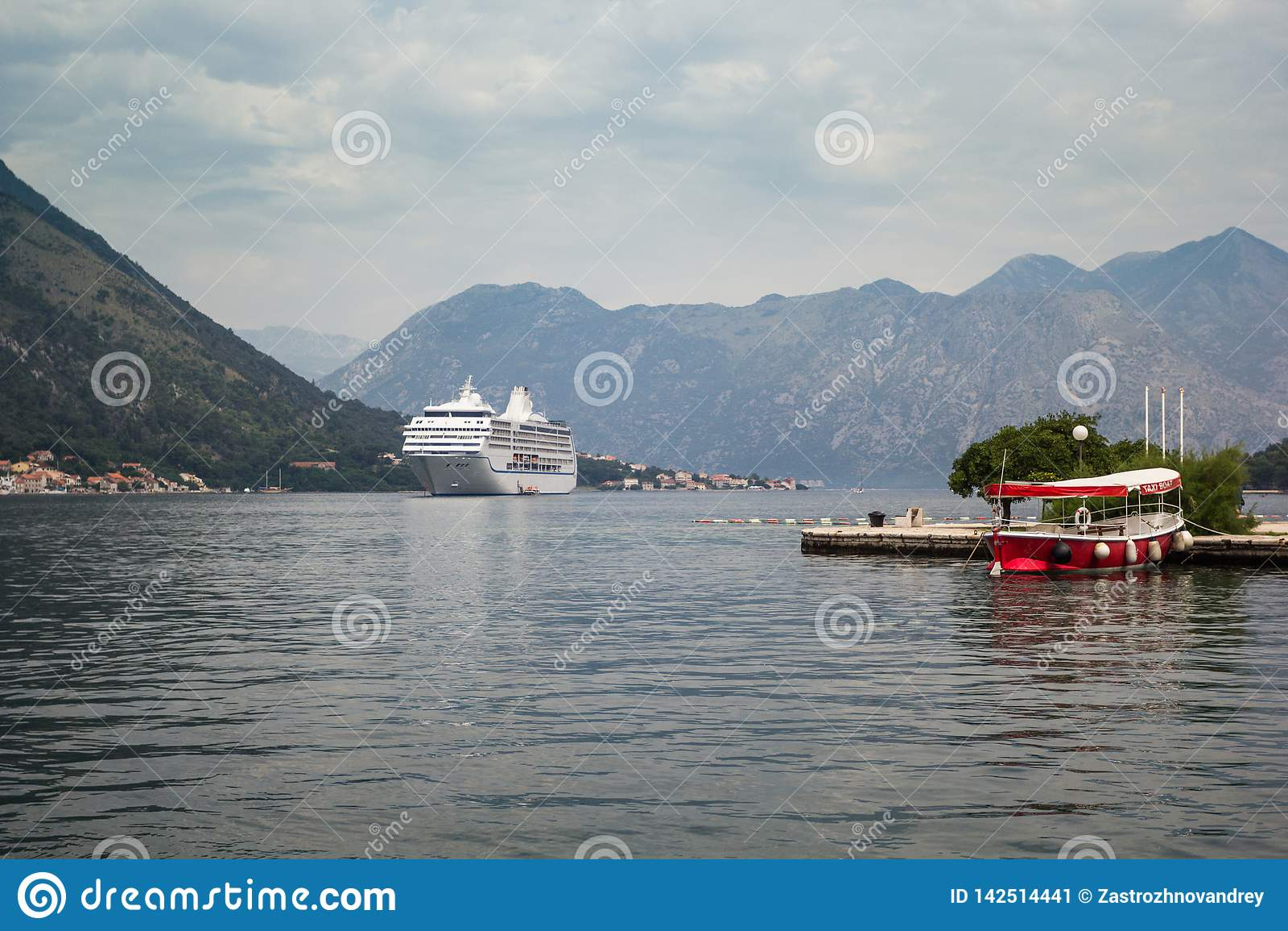 在海湾在山之间,在码头的出租汽车小船的游轮在前景