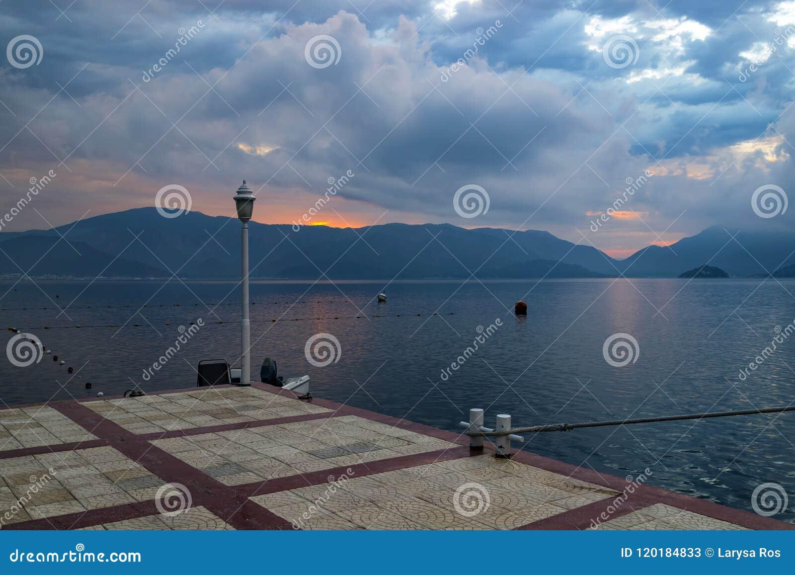 在海滨的美丽如画的日出,朝阳的光芒通过美丽的云彩做他们的方式