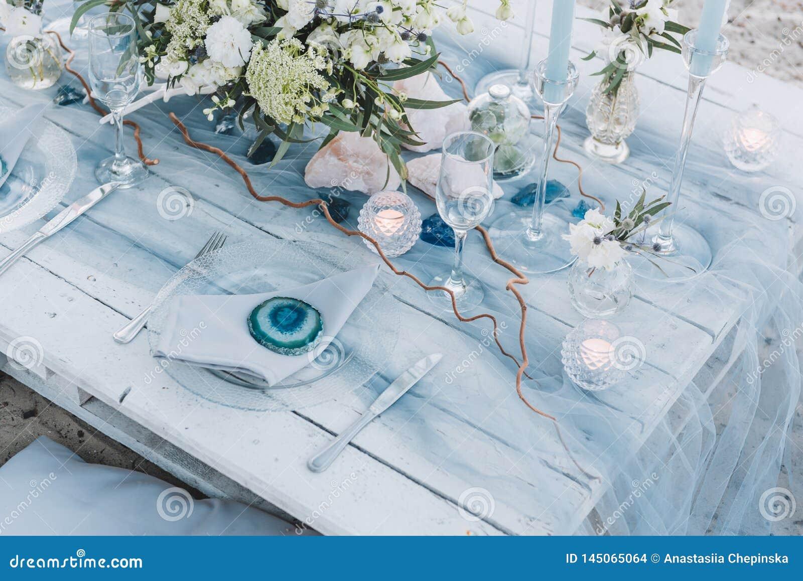 在海滩婚礼的蓝色柔和的淡色彩设定的典雅的桌