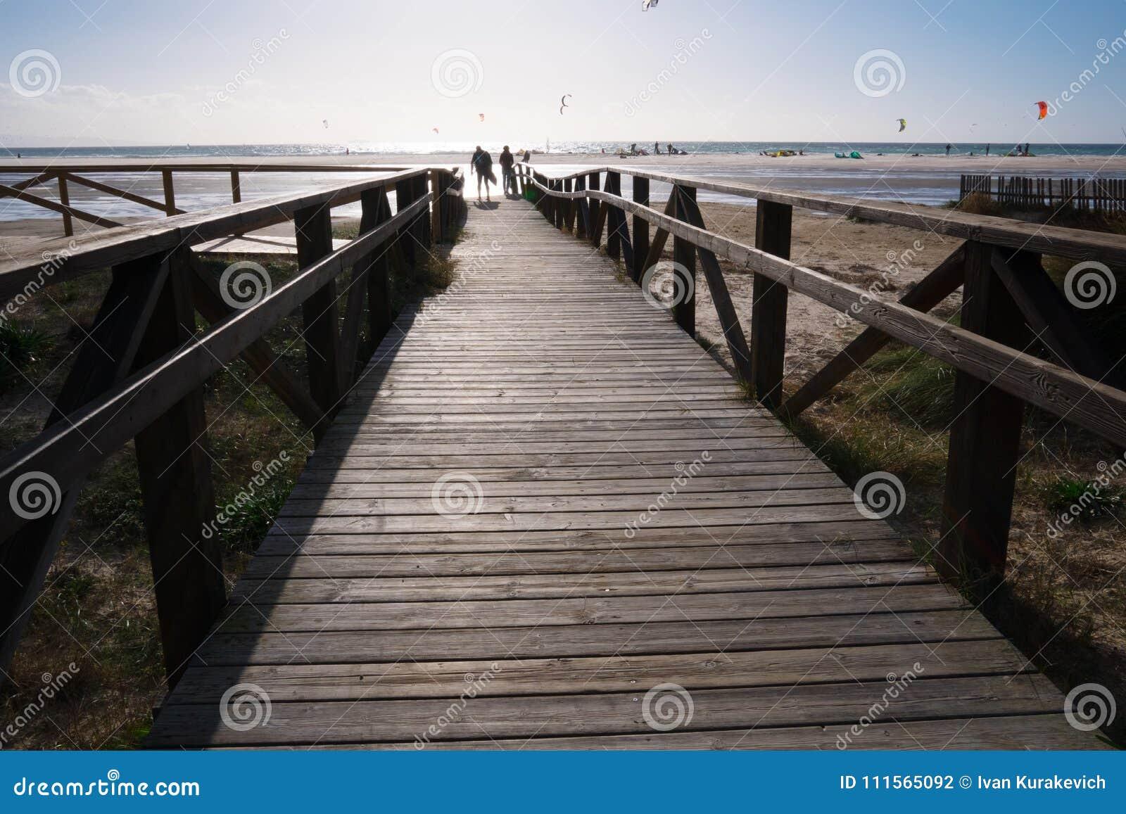 在海滩的木桥与在风暴前的黑暗的云彩在塔里法角,西班牙