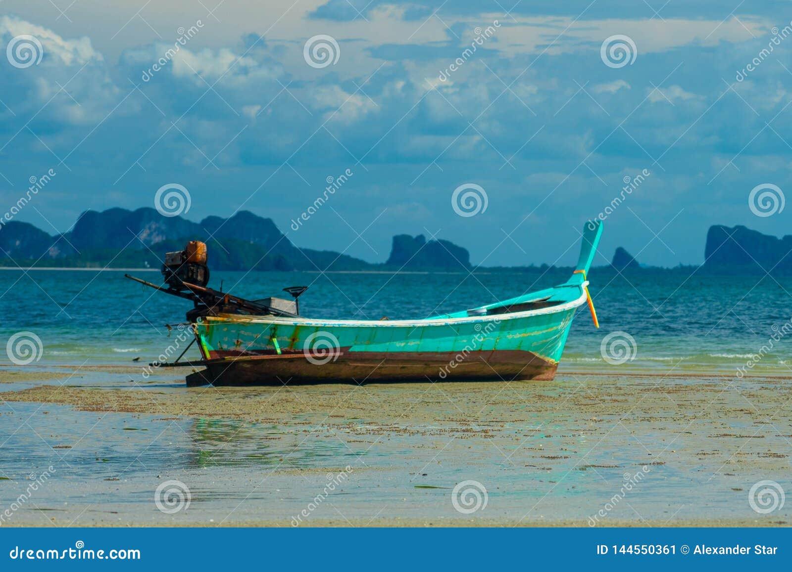 在海滩的蓝色泰国帆船附载的大艇