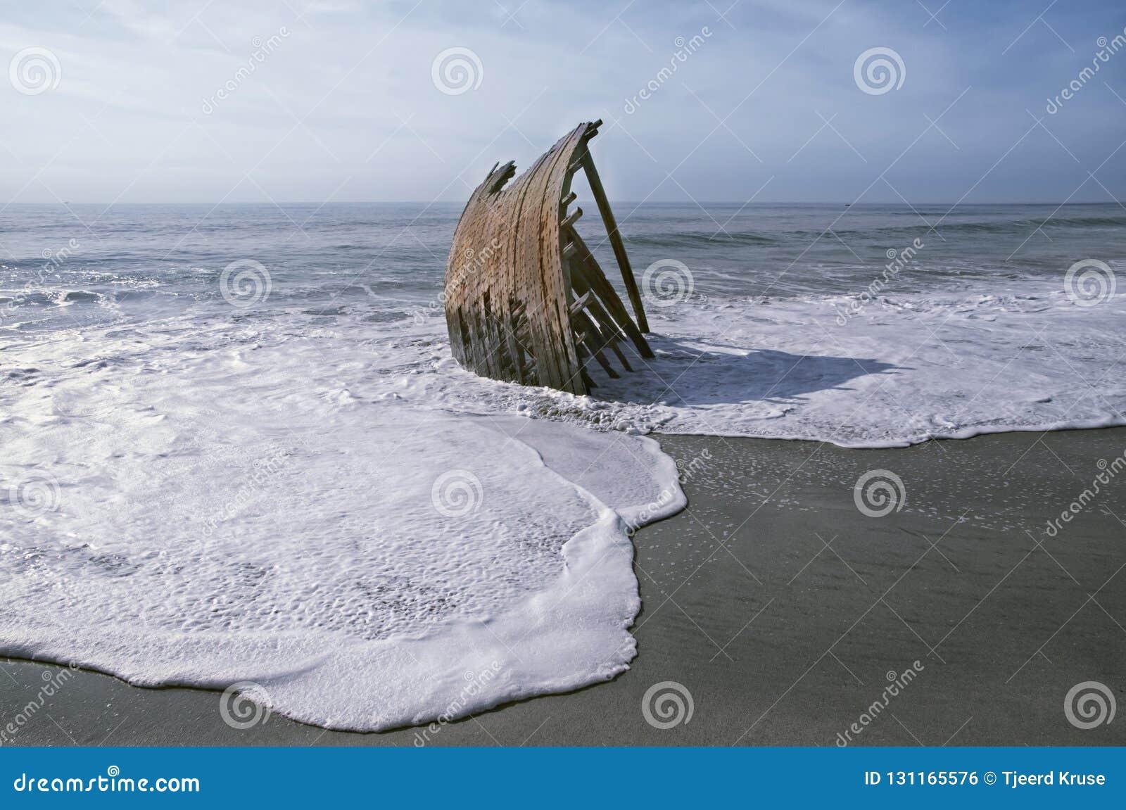 在海滩的被击毁的单桅三角帆船