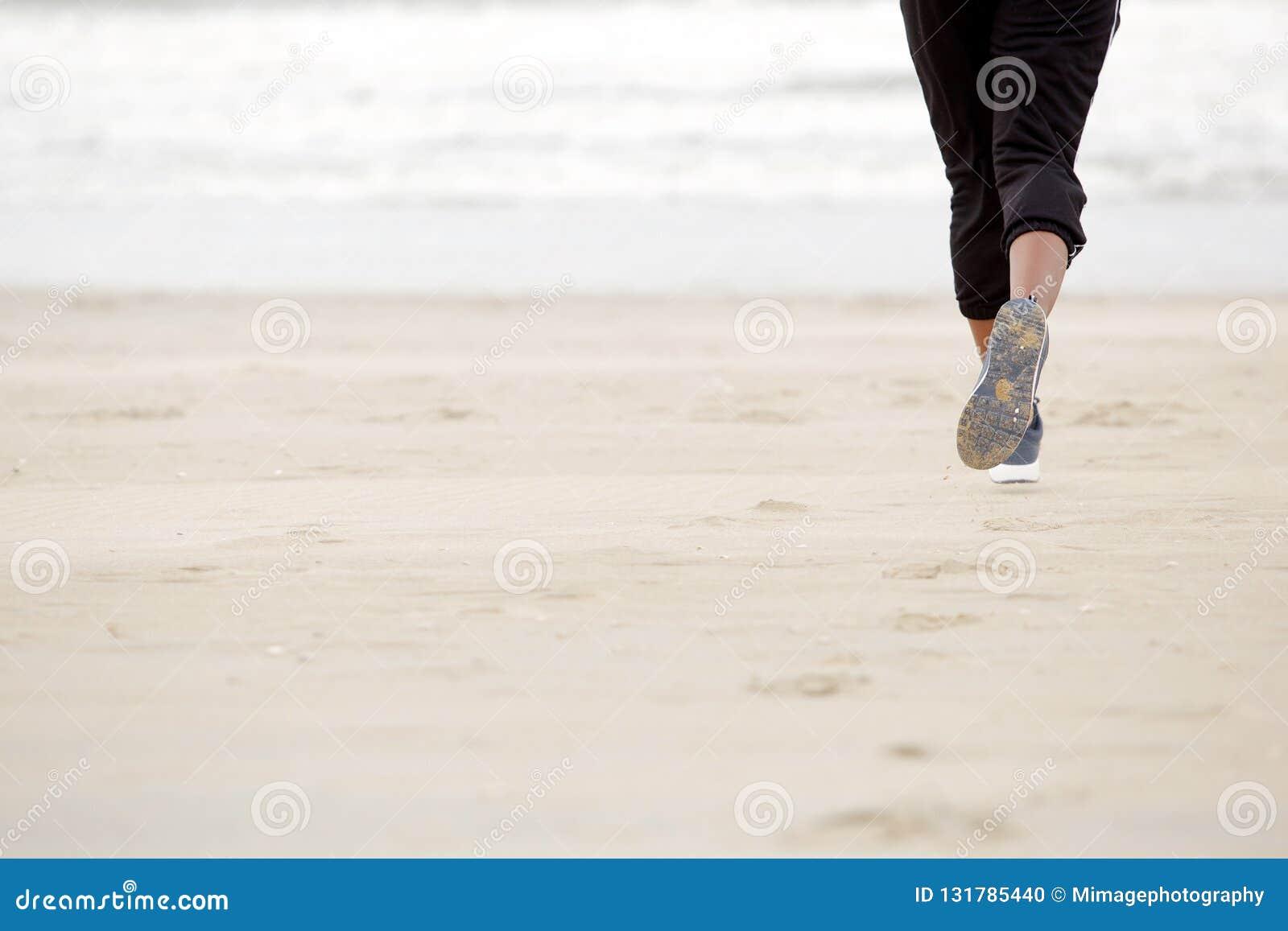 在海滩的非裔美国人的女性赛跑与体操鞋