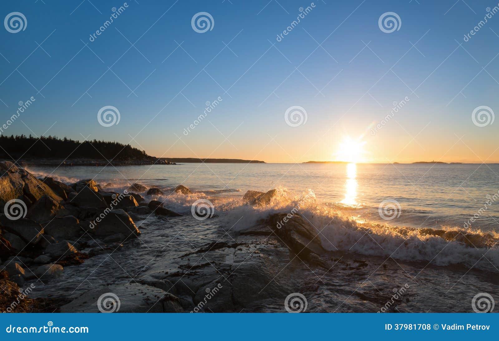 在海洋海滩(水晶新月形海滩,新斯科舍,加拿大)的冬天日出.图片