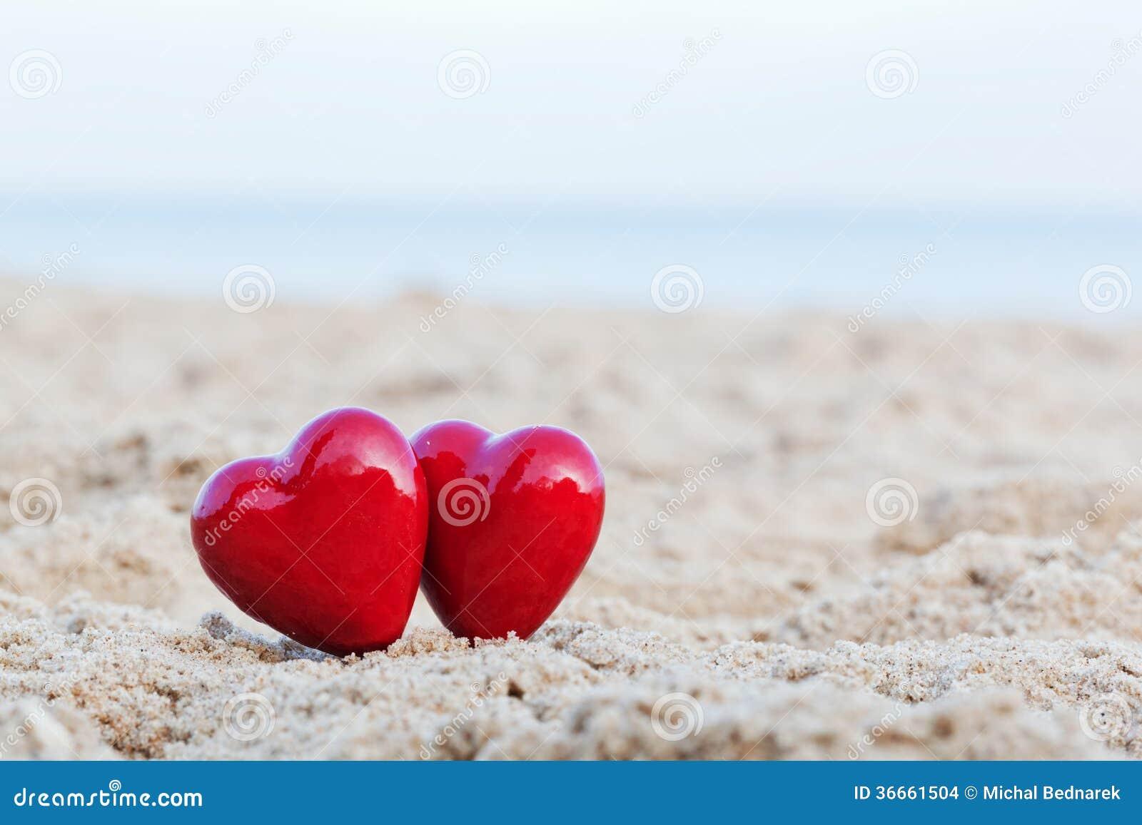 在海滩的两红色心脏。爱