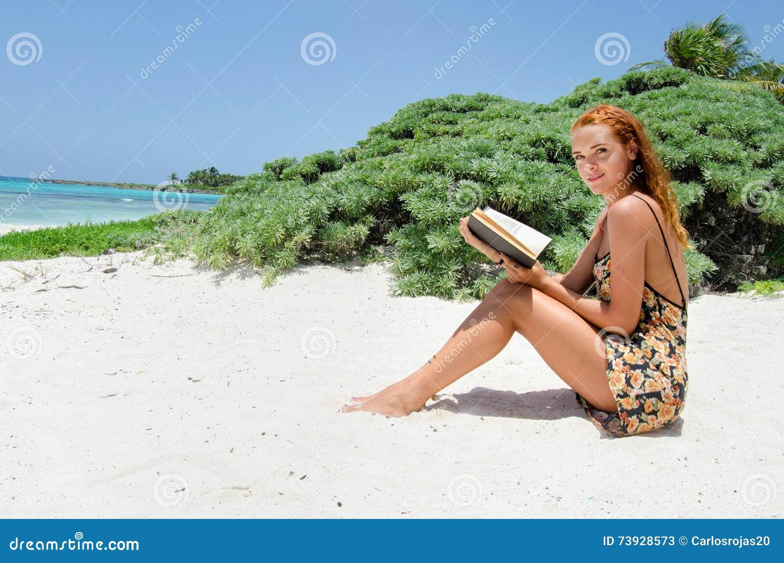 在海滩的妇女读书