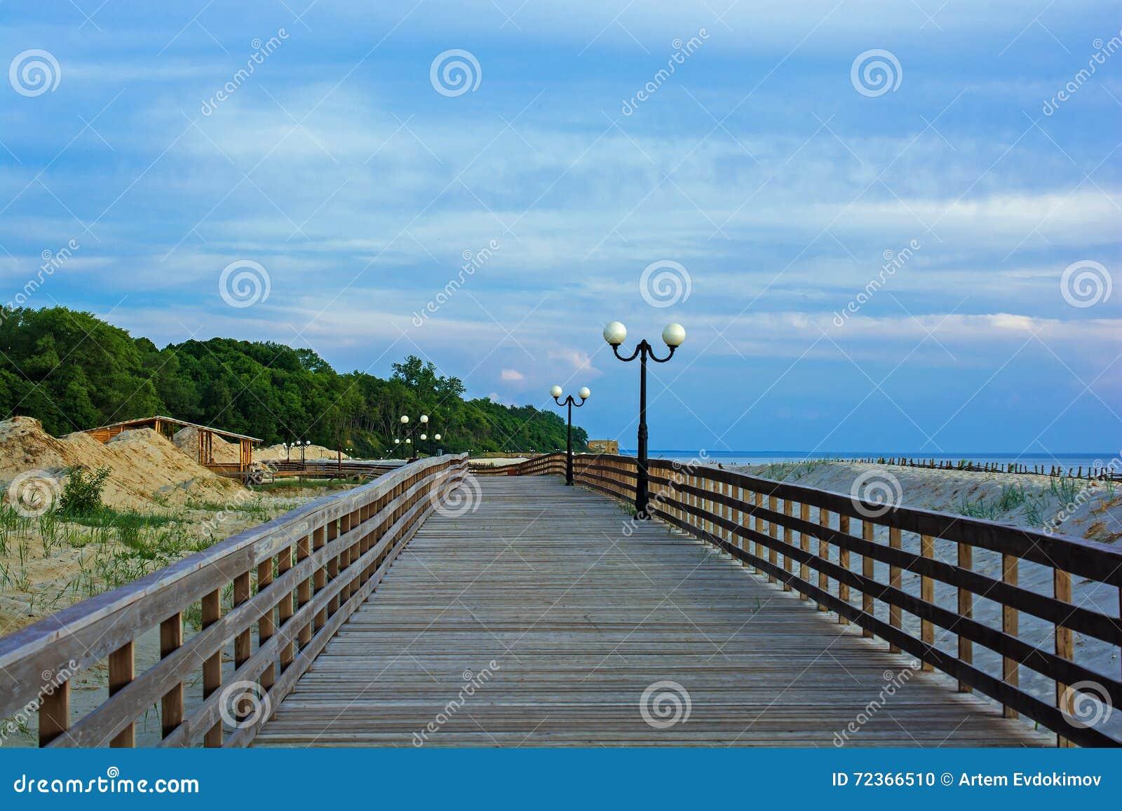 在海滩的木散步与在日落的路灯柱在波罗地
