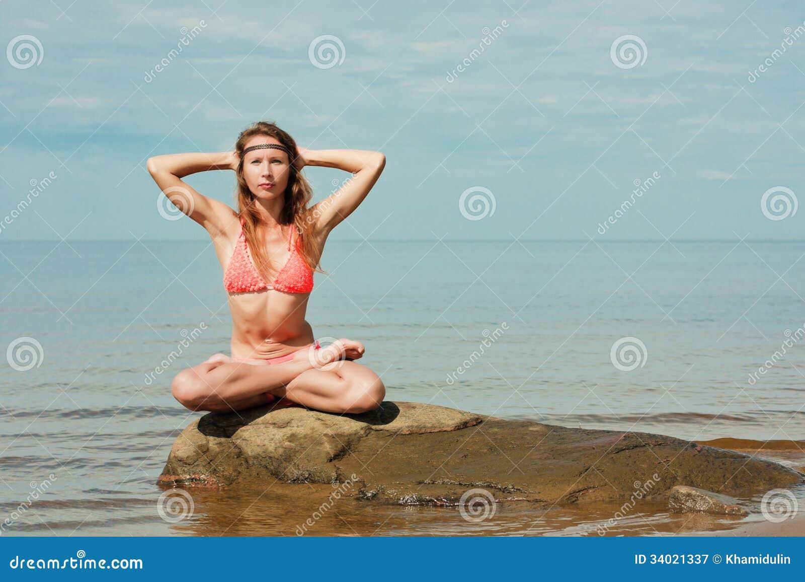 在海滩的美好的女子瑜伽