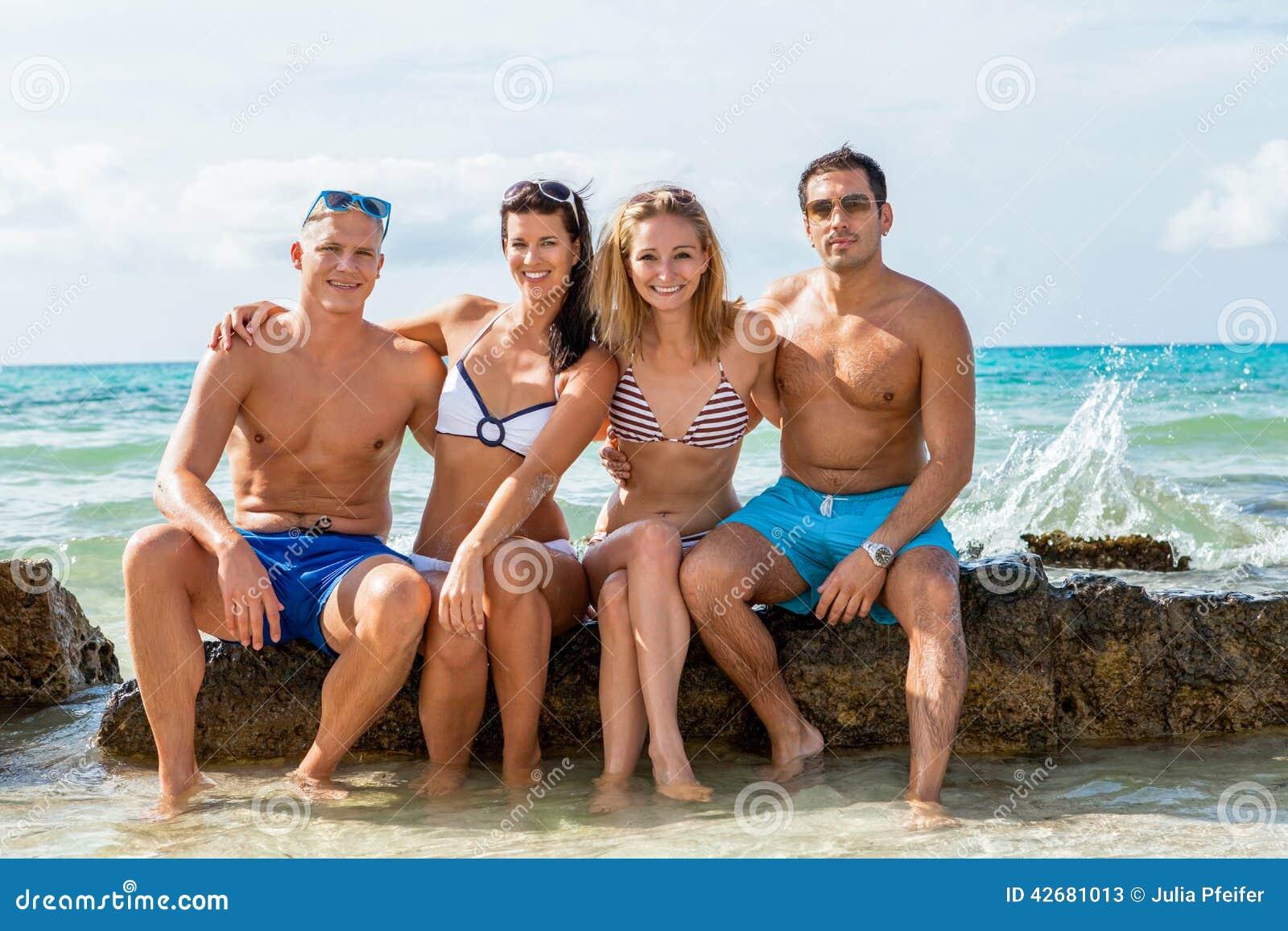 在海滩的年轻愉快的朋友havin乐趣